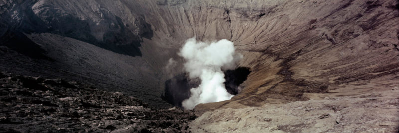 A cloud billows from the crater of a volcano