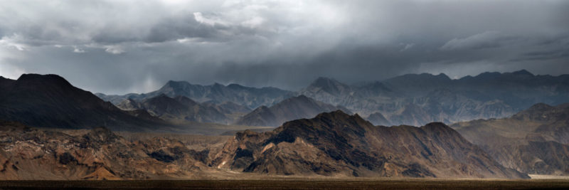 Dark cloud loom over the mountains of death valley
