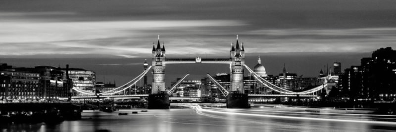 The Tower Bridge raised at night in london city