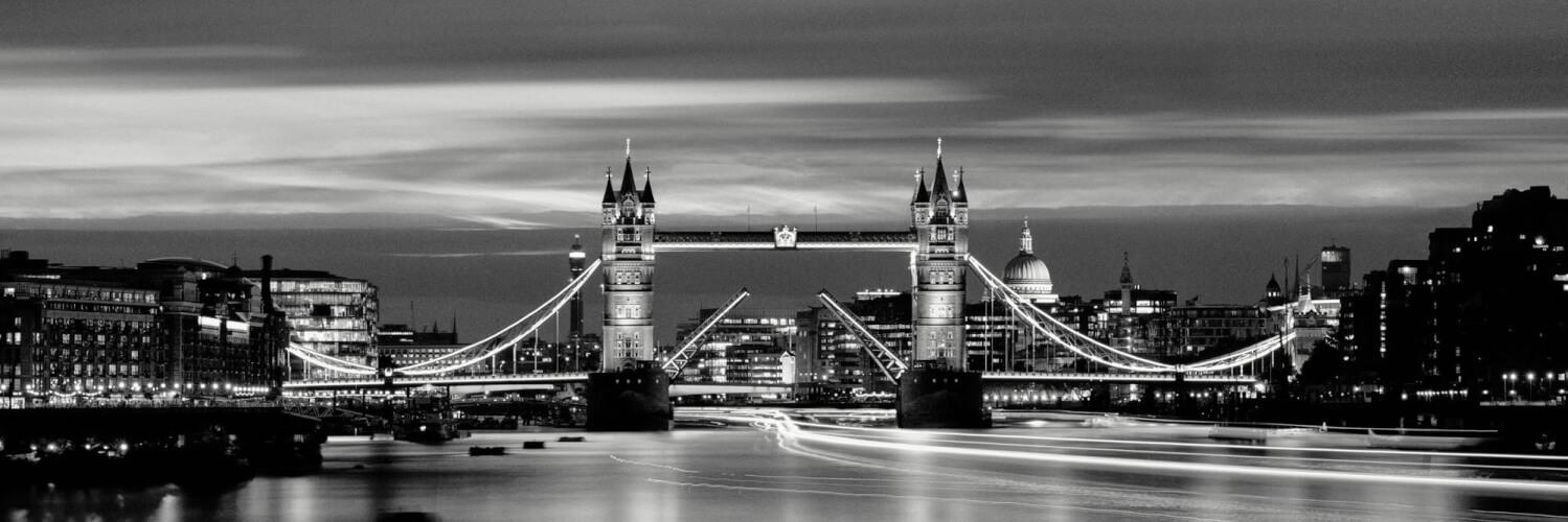 The Tower Bridge raised at night in london city
