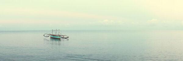Fishing boat in the vast calm ocean