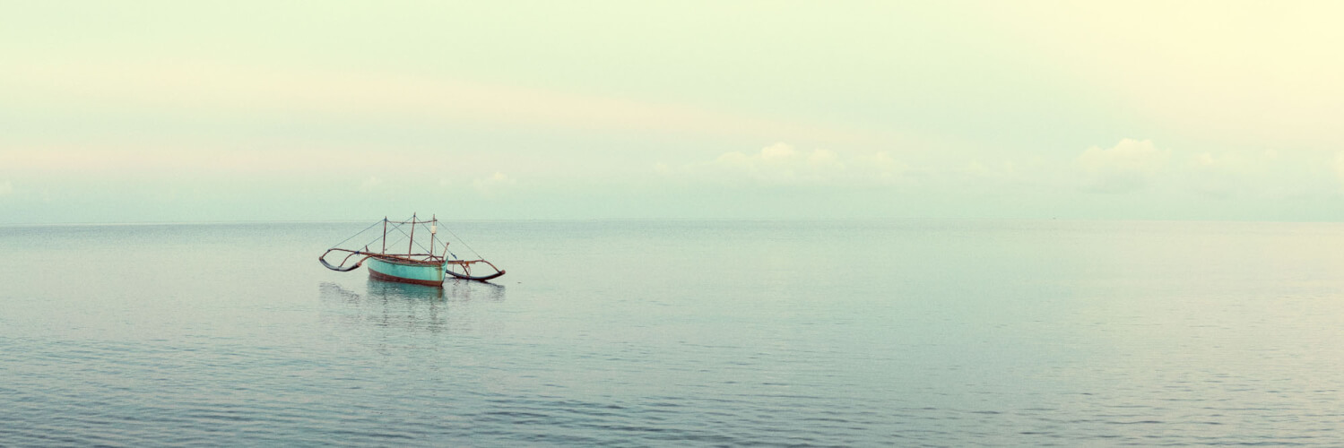 Fishing boat in the vast calm ocean