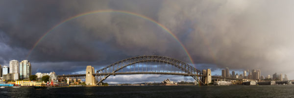 A Rainbow over Sydney harbour with the city in the backdrop