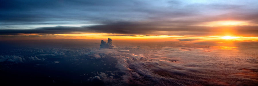 Beautiful Sunset high above the clouds from a plane window