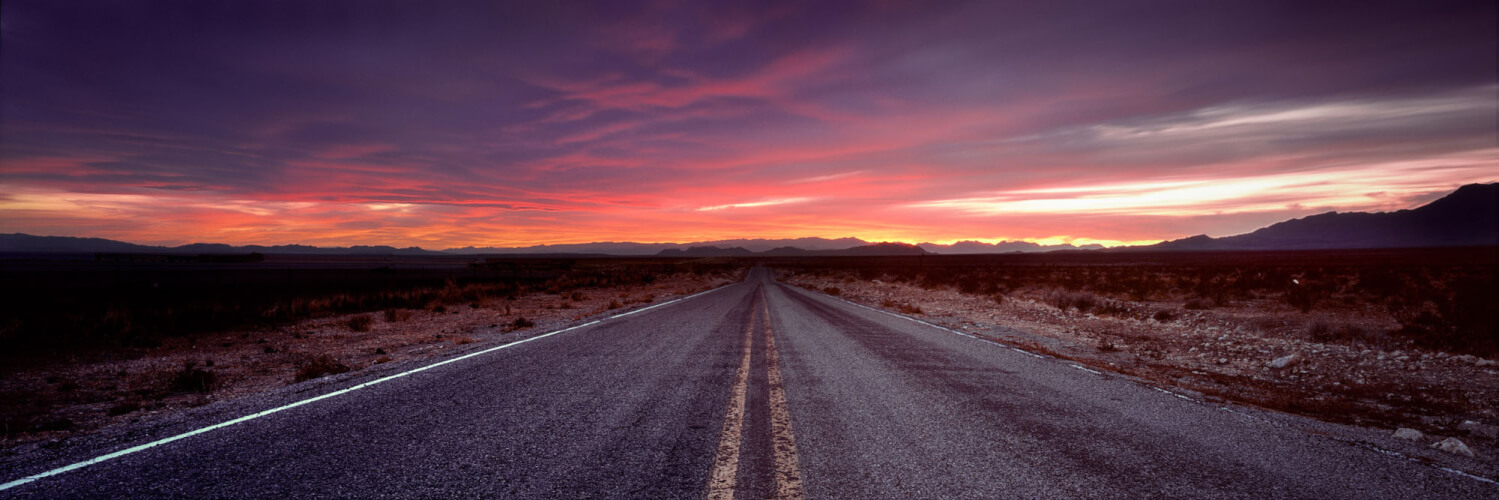 Long straight US road leading to sunset