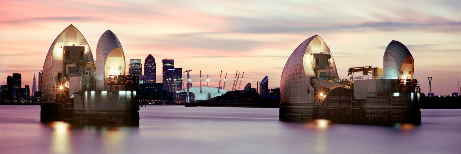 The thames river barrier with Canary wharf in the background at sunset