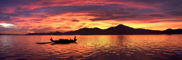 Fishing boat crosses the lagoon as a beautiful sunrise lights up the sky