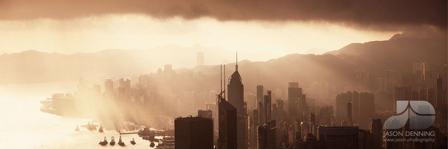 sun rays shining over hong kong city