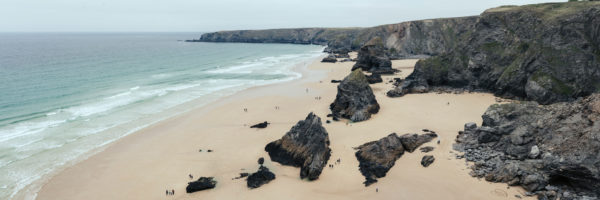 A panoramic print of Bedruthan beach as people walk around