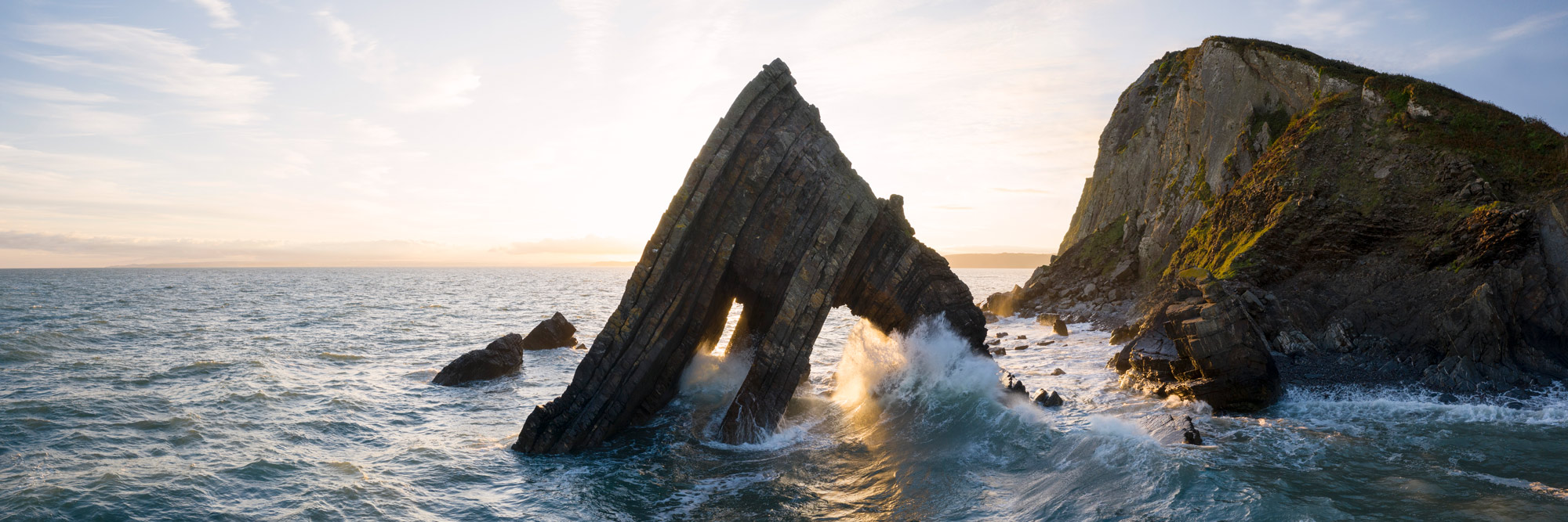 A panoramic print as a wave crashes against rocky coastline