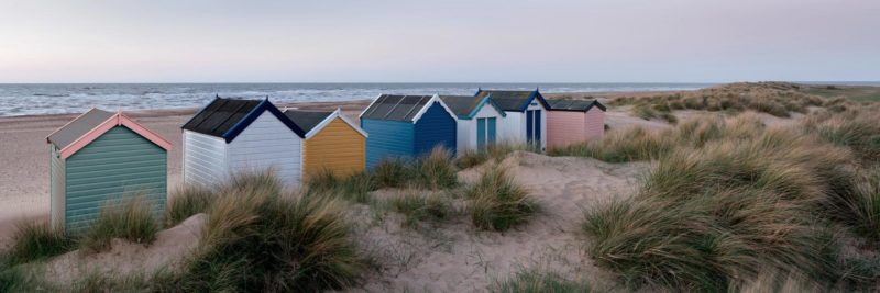 Colourful Beach huts at dawn on an English beach