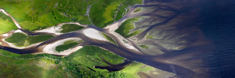 An aerial print of a river flowing into a Scottish lock