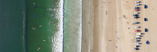 Aerial of surfers riding a wave at inch beach in Ireland