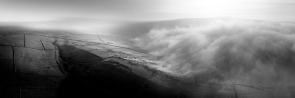 a panoramic print as fog passes through the Yorkshire Dales in black and white