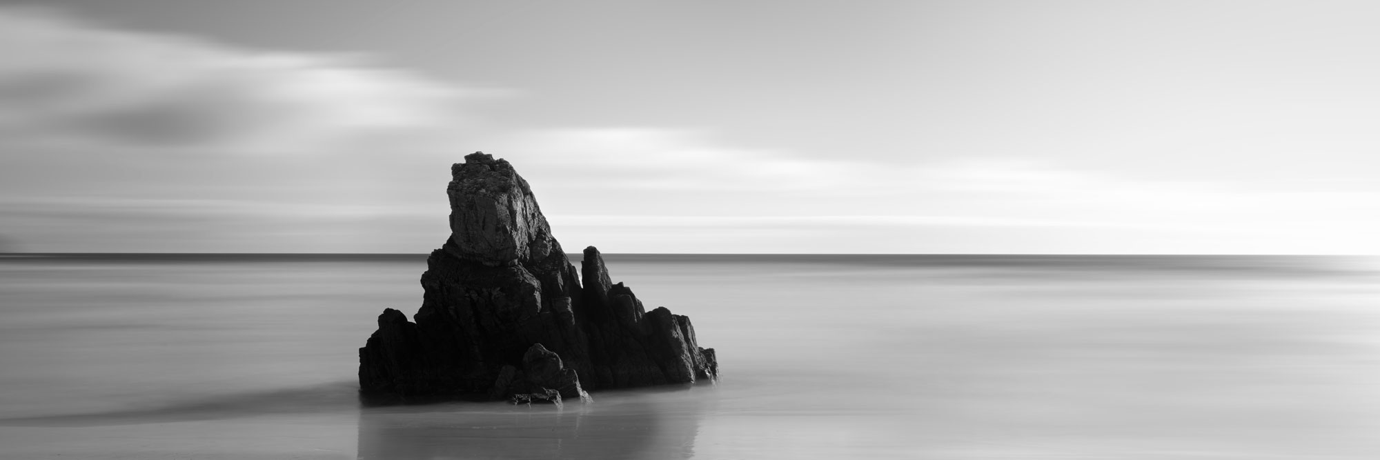 abstract Lone rock on a beach black and white