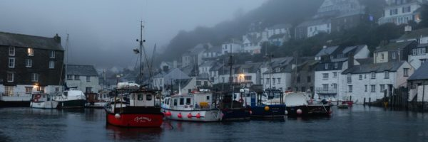 Panorama of Polperro Harbour and fishing boats during morning mist along the south west coast path in Cornwall